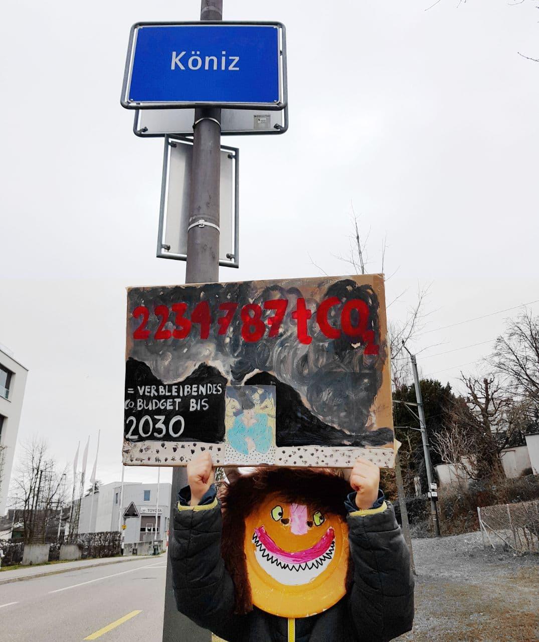 Person mit Karnevalsmaske hält ein Plakat mit dem verbleibenden CO2 Budget der Gemeinde Köniz bis 2030