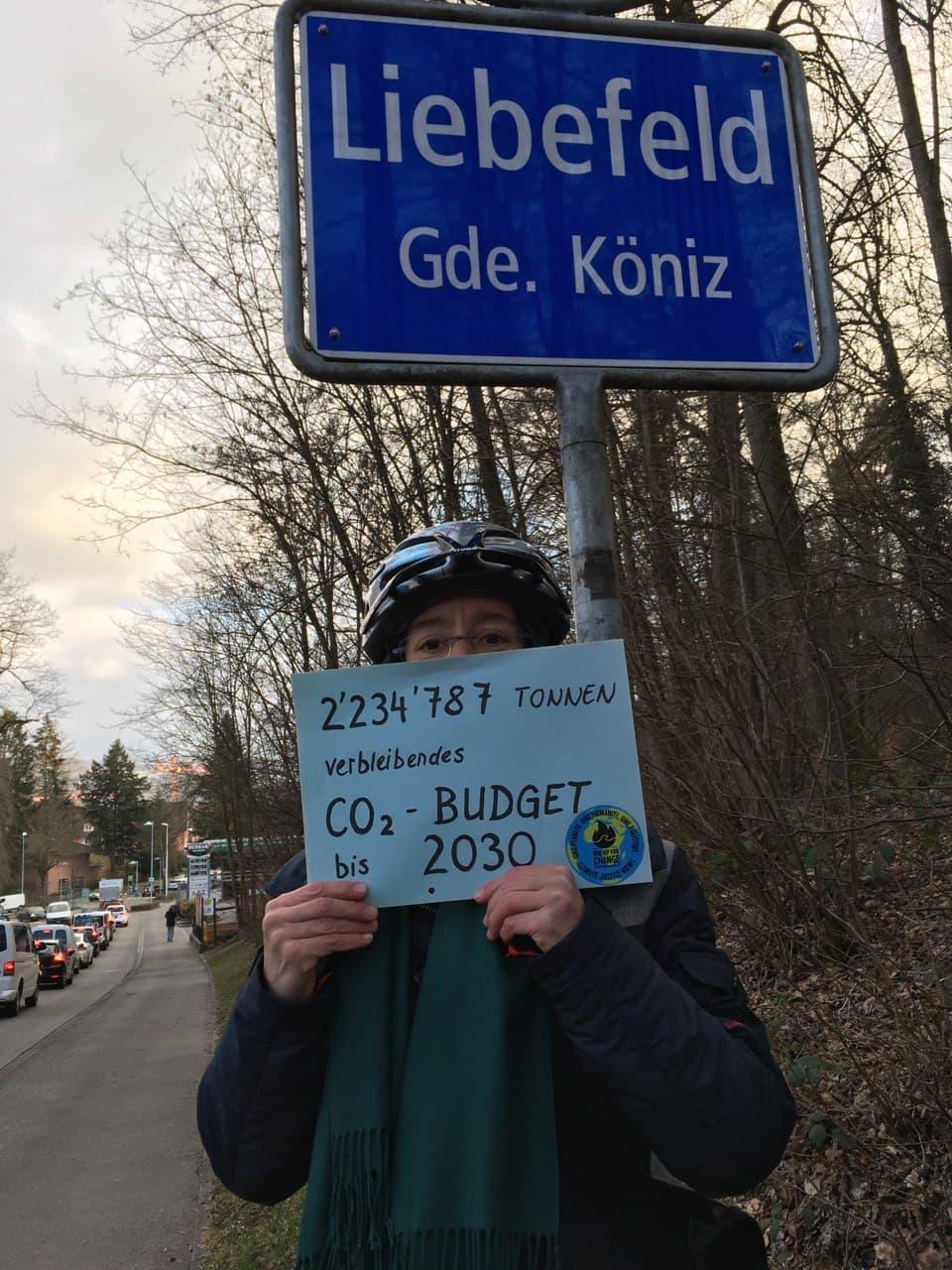 Person mit Plakat mit CO2 Budget der Gemeinde Liebefeld