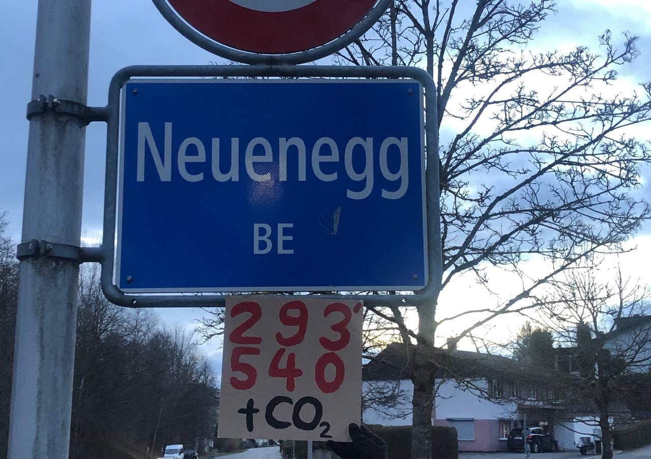 Plakat mit CO2 Budget der Gemeinde Neuenegg hängt an Gemeindeschild